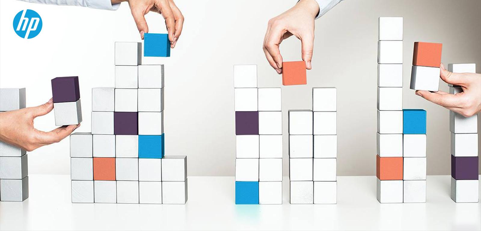 manos construyendo torres con cubos